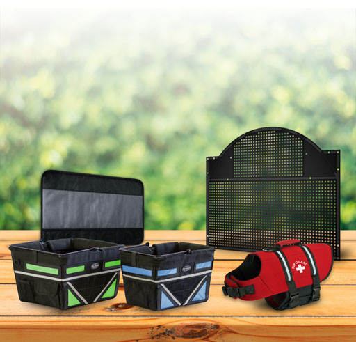 Travelin-k9 Products on a wooden table with a green bush background, Pet-Pilot, Dog Basket Life Jacket, Pet Net, Door Shield